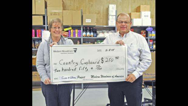 Don Haynes presenting a donation to Carol Hoffman for the Country Cupboard Food Pantry.