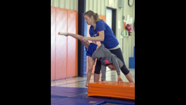 Abby shown guiding a student through a cartwheel.