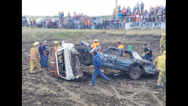 Safety first. Members of the Philip Volunteer Fire Department quickly checked the driver, then were wary of sparks and the car falling the wrong way as they got these two cars down. Then, the demolition derby heat roared on.