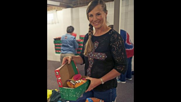 Lavonne Kinsley, head of the Operation Christmas Child program at Community Bible Church fills a shoe box with items in preparation to be sent out.