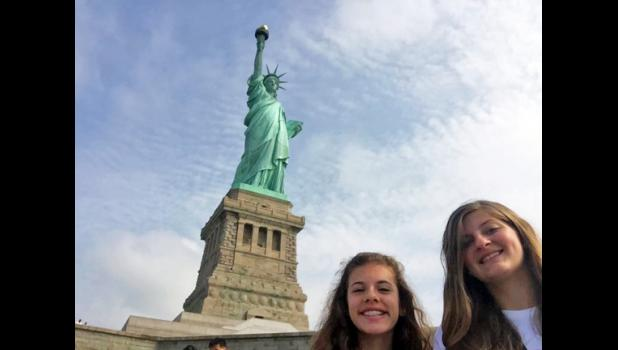 Lilli Moore and Emily Jacobs pose beside New York City's Statue of Liberty.