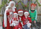 Santa, Mrs. Claus, an elf take time to pose with children.